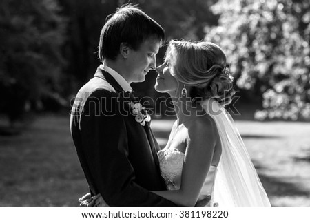 Cheerful romantic couple of newlyweds hugging in summer park b&w