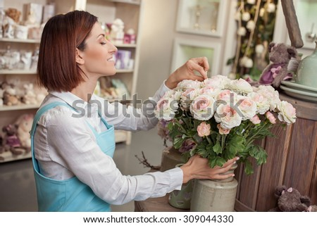 Cheerful saleswoman is caring of flowers in her workshop. She is standing and smiling. The woman is touching roses and looking at them with inspiration - stock photo