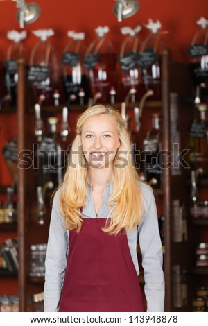 cheerful saleswoman with apron standing in gourmet store