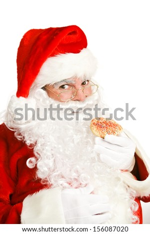 Cheerful Santa Claus eating a Christmas cookie.  White background.   - stock photo