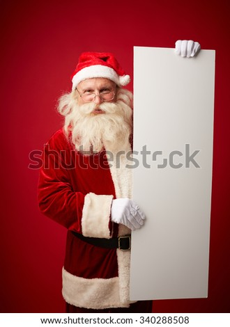 Cheerful Santa Claus holding blank paper poster - stock photo