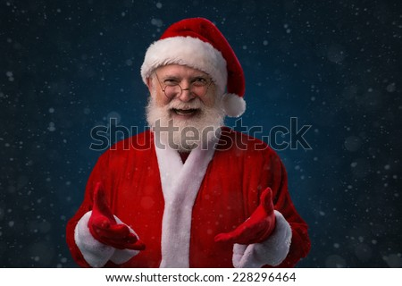 Cheerful Santa Claus holding something in his hands - stock photo