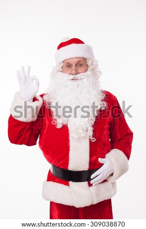 Cheerful Santa Claus is showing okay sign. He is smiling and looking forward with joy. Isolated on background - stock photo