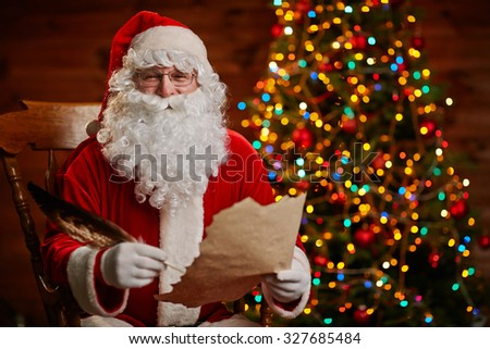 Cheerful Santa with paper and feather looking at camera while writing Christmas letter
