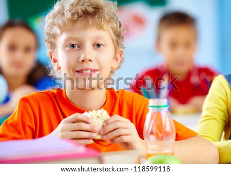 Cheerful schoolboy looking at camera while having lunch during break with his classmates behind - stock photo