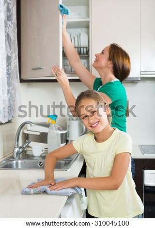 Cheerful schoolgirl helping mother dusting furniture indoor. Focus on girl - stock photo