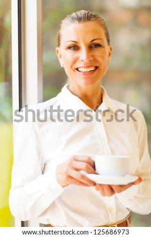 cheerful senior businesswoman with coffee in office