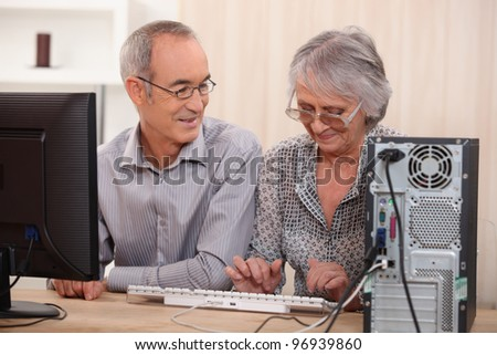 Cheerful senior couple browsing on the Internet - stock photo