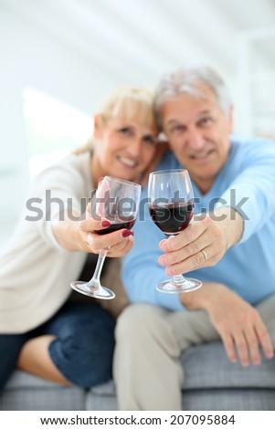 Cheerful senior couple cheering with glass of wine - stock photo