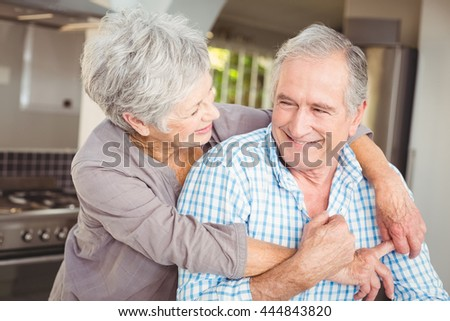 Cheerful senior couple embracing in kitchen at home - stock photo