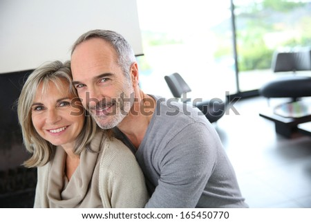 Cheerful senior couple enjoying fireplace in winter - stock photo