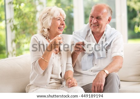 Cheerful senior couple having delicious morning coffee indoor