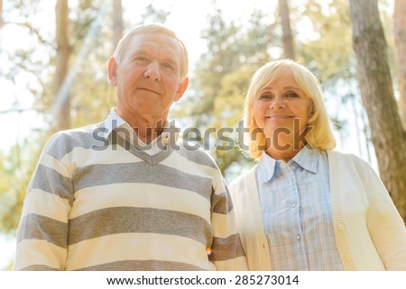 Cheerful senior couple. Low angle view of cheerful senior couple looking at camera and smiling while standing close to each other outdoors - stock photo