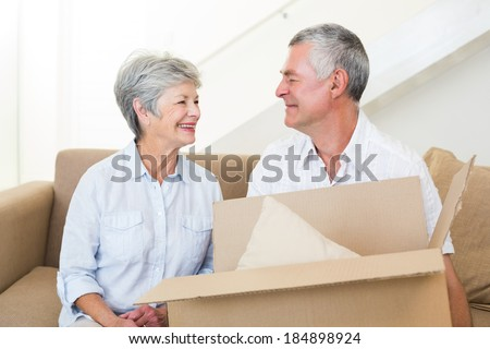 Cheerful senior couple moving into new home smiling at each other - stock photo