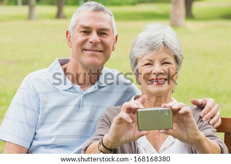 Cheerful senior couple photographing themselves while sitting on bench at the park - stock photo