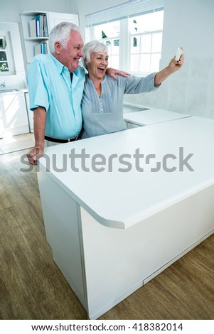 Cheerful senior couple taking selfie through mobile phone at home - stock photo