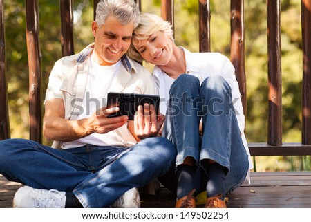 cheerful senior couple using tablet computer outdoors - stock photo