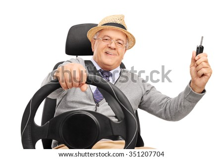 Cheerful senior gentleman sitting on a car seat and holding a car key isolated on white background - stock photo