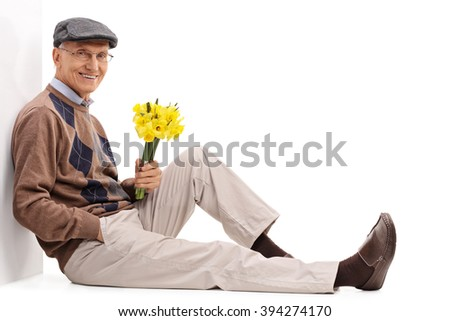 Cheerful senior gentleman sitting on the floor and holding a bunch of flowers isolated on white background - stock photo