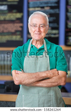 Cheerful senior male in apron standing in cafe - stock photo