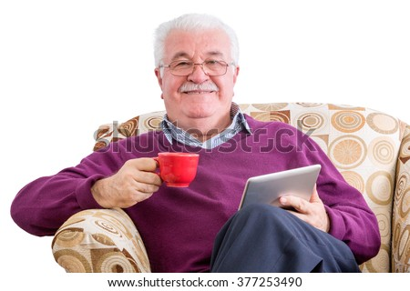 Cheerful senior male in purple sweater holding tablet computer in one hand and a red mug in the other while relaxing in chair over white background - stock photo