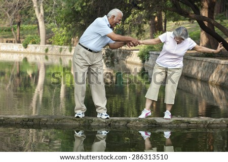 Cheerful senior man and woman having fun at park - stock photo