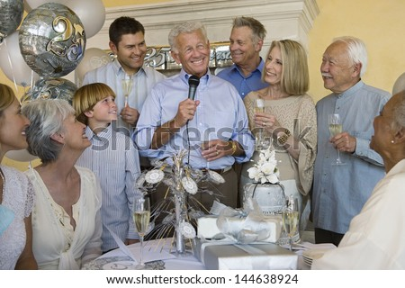 Cheerful senior man celebrating start of retirement with family and friends - stock photo
