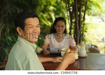 Cheerful senior man drinking tea with his wife