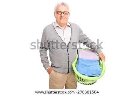Cheerful senior man holding a laundry basket and looking at the camera isolated on white background - stock photo
