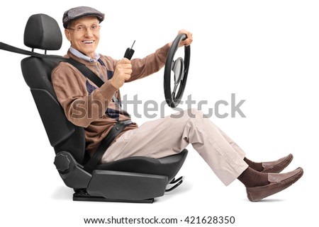 Cheerful senior man holding a steering wheel and a car key seated on a vehicle seat isolated on white background - stock photo