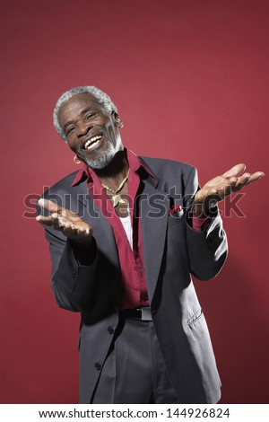 Cheerful senior man in suit making hand gesture against red background - stock photo