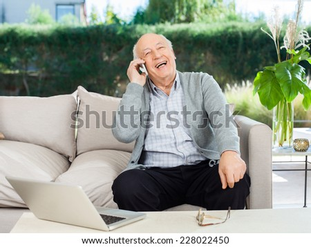 Cheerful senior man laughing while answering smartphone on couch at nursing home porch - stock photo