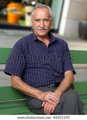 Cheerful senior man sitting outdoor on bench in the City