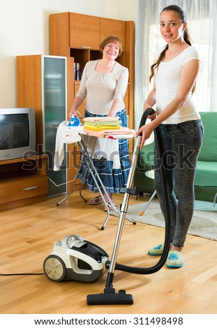 Cheerful senior mature woman and her adult daughter cleaning together at home