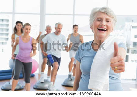 Cheerful senior woman gesturing thumbs up with people exercising in the background at fitness studio - stock photo