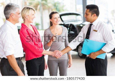 cheerful senior woman handshaking with car sales consultant at dealership - stock photo