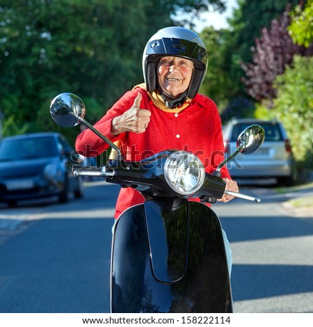 Cheerful senior woman on a scooter. Smiling old lady on a scooter stopped in the street facing the camera giving a thumbs up of approval to show her enjoyment of this mode of transport - stock photo