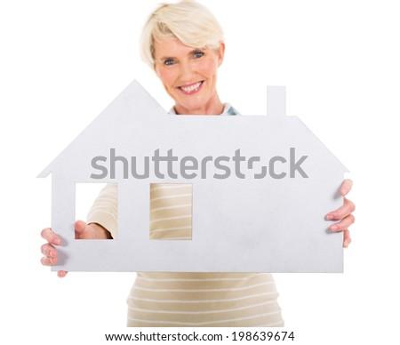 cheerful senior woman presenting white paper house - stock photo