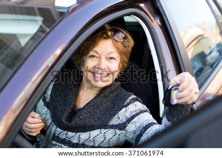 Cheerful senior woman sitting in new car at driver seat - stock photo