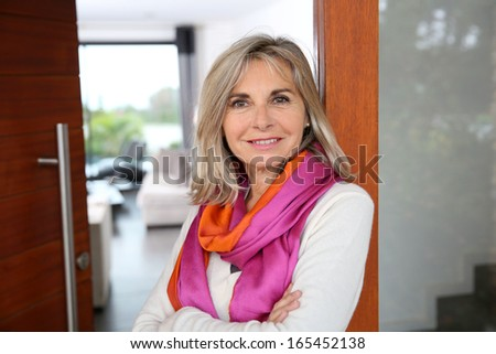 Cheerful senior woman standing at home entrance door - stock photo