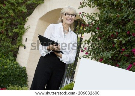 Cheerful senior woman standing by sign board with clipboard while looking away - stock photo