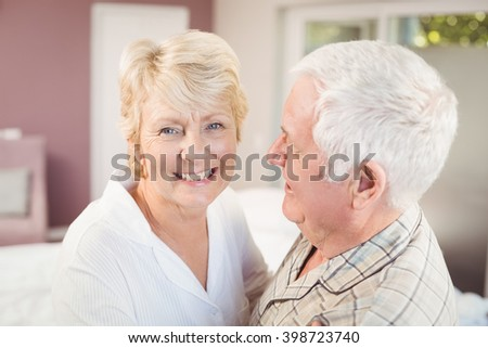 Cheerful senior woman with husband in nightwear at home - stock photo