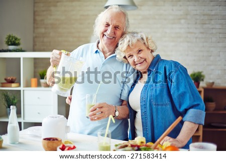 Cheerful seniors having fresh smoothie in the kitchen - stock photo