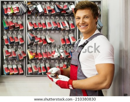 Cheerful serviceman near stand with colour samples in car body workshop - stock photo