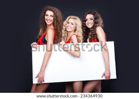 Cheerful sexy girls hold the blank placard with copy text. Greeting card - stock photo