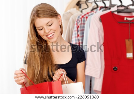 Cheerful shopping woman looking into her bag in store. Young smiling female buyer purchasing clothes.
