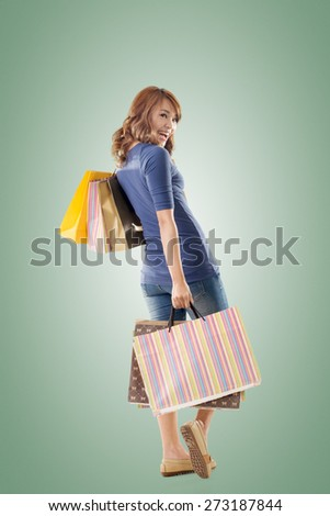 Cheerful shopping woman of Asian holding bags, full length portrait isolated. - stock photo