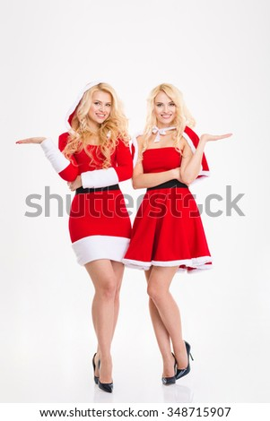 Cheerful sisters twins in santa claus costumes holding copyspace on palms over white background