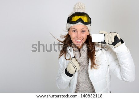 Cheerful skier woman showing ski pass