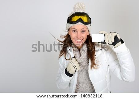 Cheerful skier woman showing ski pass - stock photo